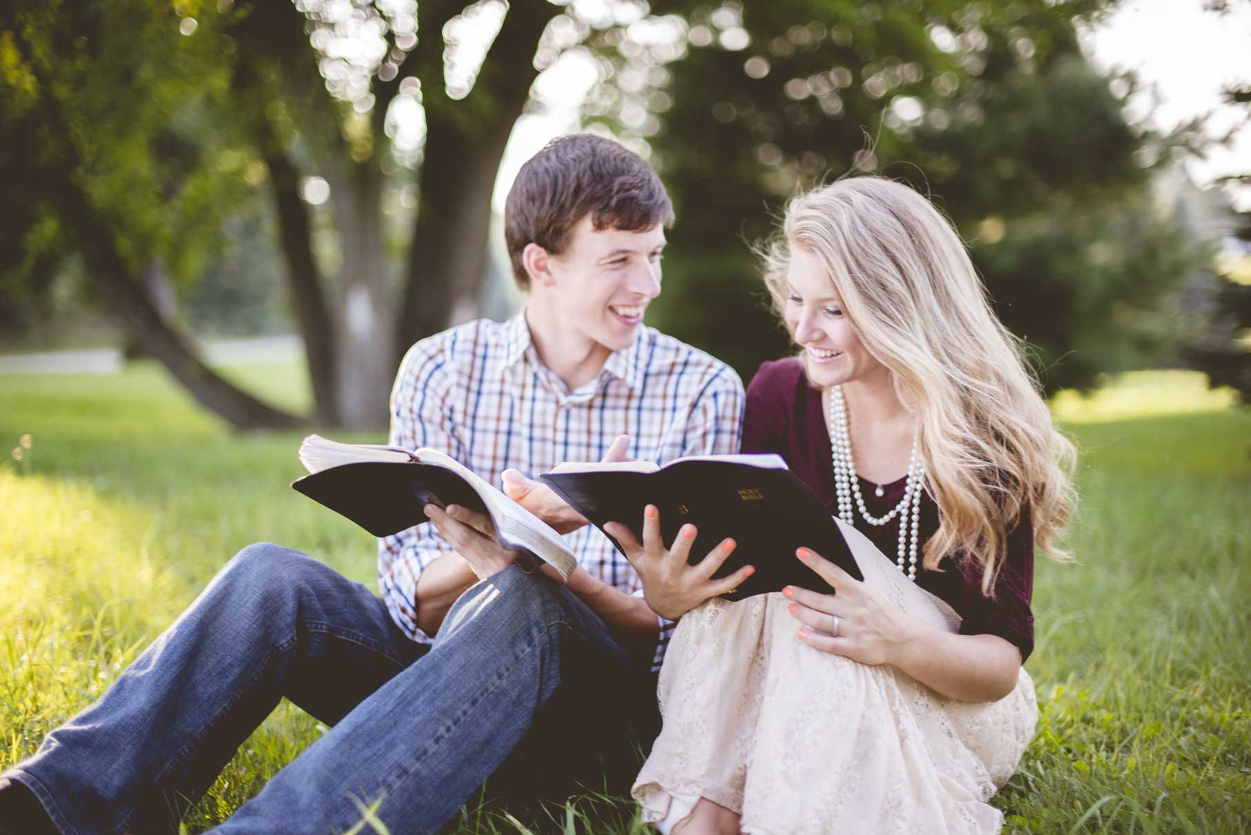 A couple reading the bible together in a garden under sunlight with a blurry background
